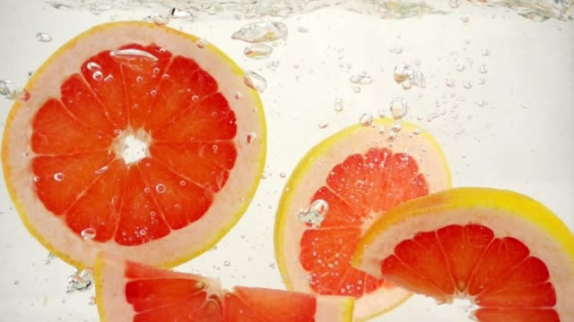 Round grapefruit slices slowly sink in water, slow motion close-up