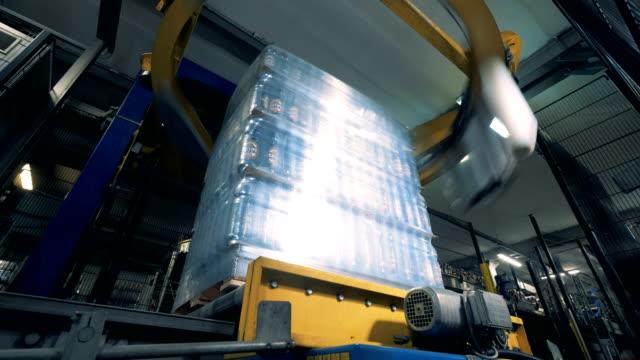 vídeos de stock, filmes e b-roll de o mecanismo industrial redondo está envolvendo blocos de frascos de cerveja no polietileno - automatizado