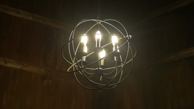 round iron chandelier hangs in a room