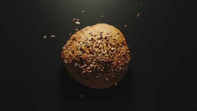 슬로우 모션: 검은 표면에 떨어지는 씨앗과 빵의 둥근 덩어리 - 식빵 한 덩어리 스톡 비디오 및 b-롤 화면