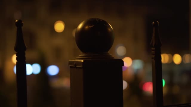 Round pillar, night city. Glowing lights behind