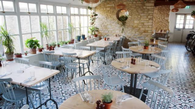 stockvideo's en b-roll-footage met ronde tafels en eend-ei blauwe stoelen in een leeg restaurant met gedessineerde vloertegels en kamerplanten kweken op de vensterbank - restaurant table