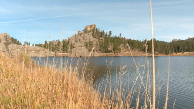 Rounded rock formations covered with trees rising above the scenic Sylvan Lake