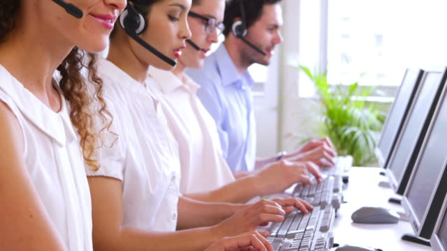 Row of call centre agents typing at their desk video
