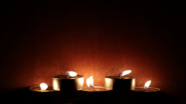 Row of candles with wooden walls in dark room. video