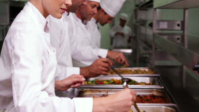 Row of chefs preparing food in serving trays video