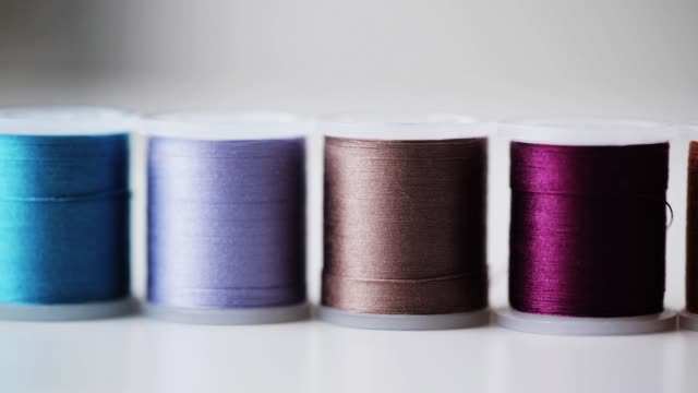 row of colorful thread spools on table - cilindro video stock e b–roll