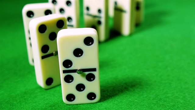 vidéos et rushes de rangée de dominos tombant sur sur fond vert - vue partielle