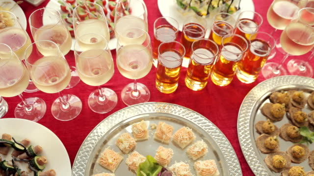 Row of glasses of alcohol and juice, a wide variety of snacks at the banquet video