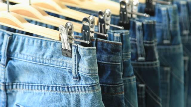 fila di hanged blue jeans - jeans video stock e b–roll