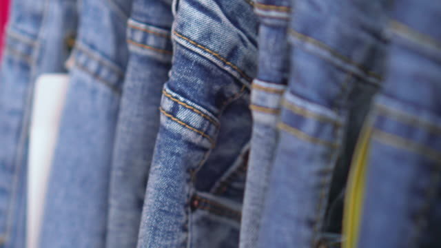 row of hanged blue jeans,dolly shot - jeans video stock e b–roll