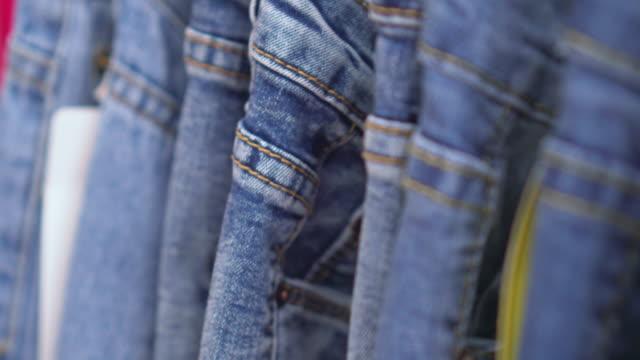row of hanged blue jeans,dolly shot - dżinsy filmów i materiałów b-roll