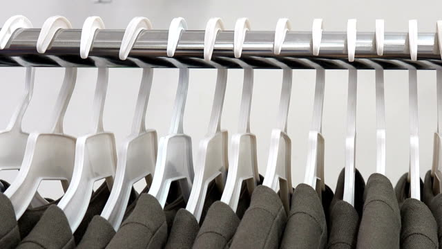 Row of jackets hanging on a rack Clothes on hangers on a garment rack in an apparel factory coathanger stock videos & royalty-free footage