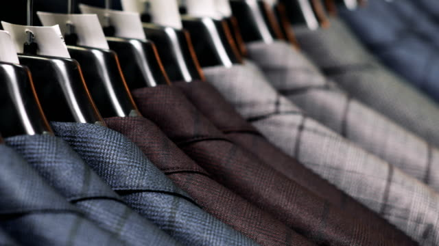 row of men suit jackets on hangers. collection of new beautiful clothes hanging on hangers in a shop - completo video stock e b–roll