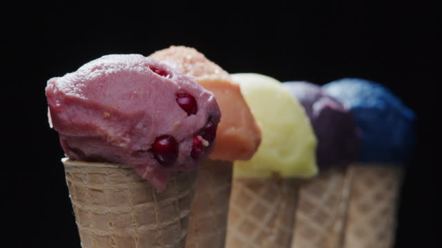 Row of multi-colored icecream cones on black background. Close-up