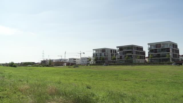 vídeos de stock e filmes b-roll de row of newly built low rise apartment buildings from grass field - plano picado