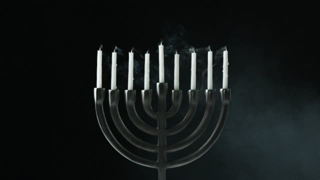 A row of nine white candles burning in a menorah are blown out, front view video