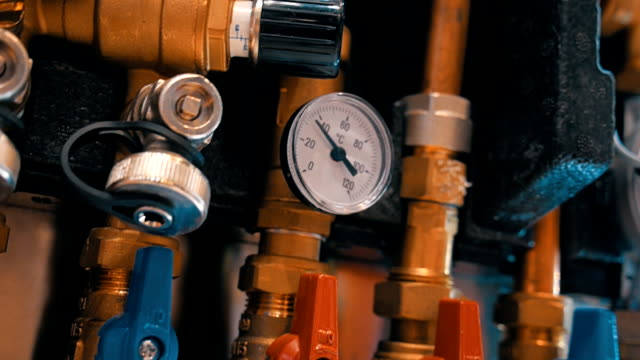 A row of red and blue water valves and pressure gauges regulating the water