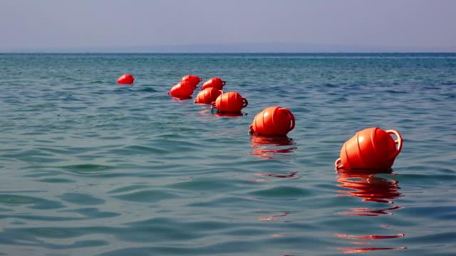 vídeos de stock, filmes e b-roll de linha de boias vermelhas no mar - boia salva vidas