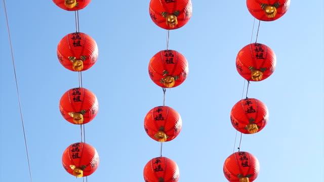 vídeos de stock, filmes e b-roll de fileira de lanternas de papel vermelho chinês com padrões ornados ouro e borlas. penduradas em fios do lado de fora. foto no fundo do céu no templo budista. - clipe