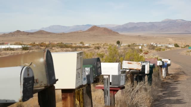 Row of vintage drop boxes on road intersection, arid Arisona desert, USA. Postal retro mailboxes on roadside of tourist Route 66. Address on old-fashioned nostalgic metal grunge postbox on pillar