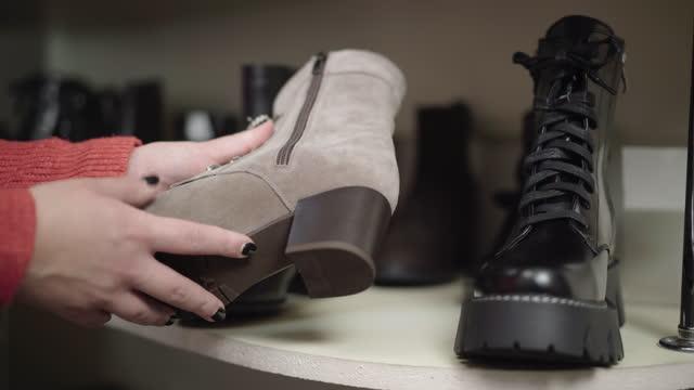 vidéos et rushes de ligne de chaussures d'hiver restant sur l'étagère avec la main caucasienne jeune femelle touchant et ramassant sur la botte. femme méconnaissable choisissant des chaussures dans le magasin. concept de vente de black friday - bottes