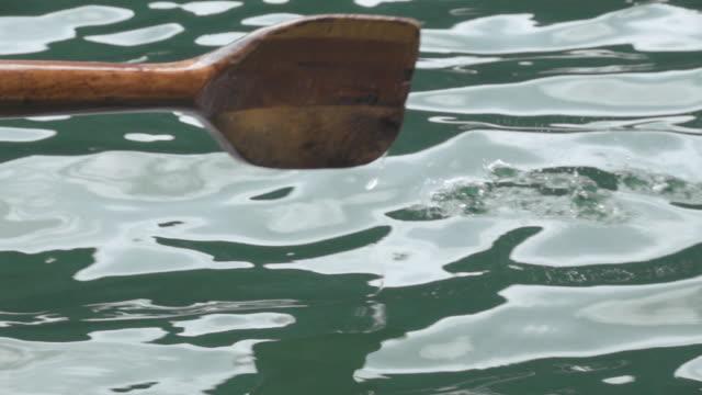 vídeos de stock, filmes e b-roll de enfileiramento um barco de madeira velho na paisagem bonita da montanha no lago áustria de hallstatt - remo atividade física