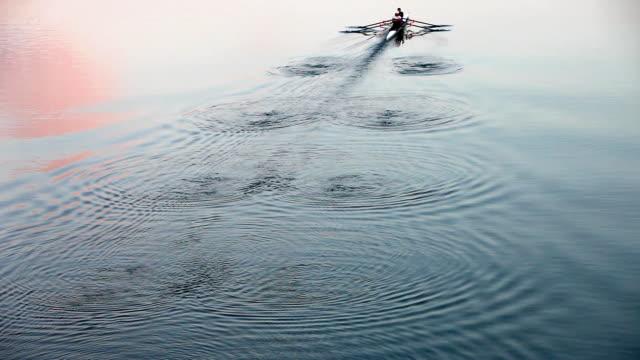 vídeos de stock, filmes e b-roll de remo ao anoitecer-se maravilhosa acenando padrão - remo esporte aquático