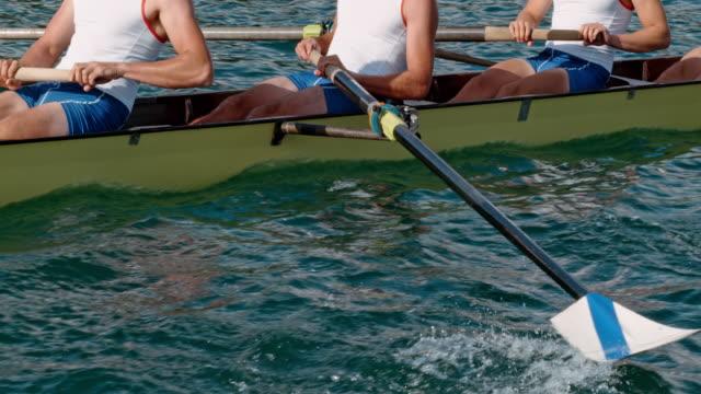 athleten die ruder durch das wasser bewegt und treibt das boot rudern - paddeln stock-videos und b-roll-filmmaterial