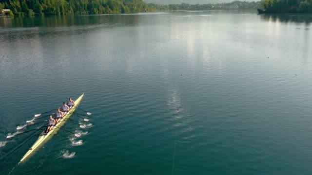 AERIAL Rowing team gliding across a lake in a quad scull