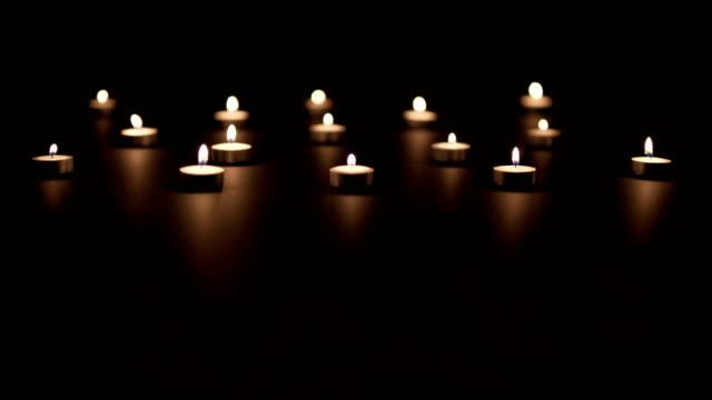 rows of candles on black - jesus christ filmów i materiałów b-roll