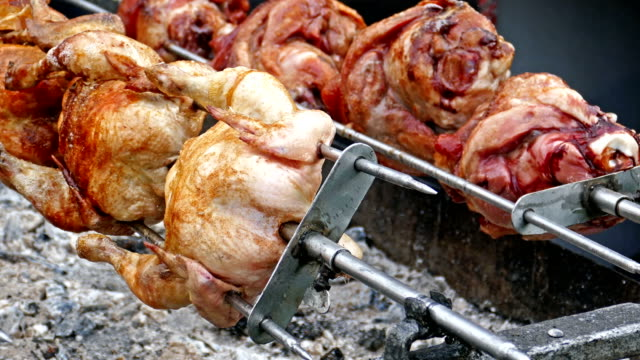 Rows of chickens and pork knuckle cooking on a rotisserie video