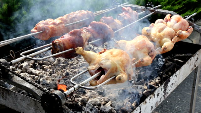 Rows of chickens cooking on a rotisserie video