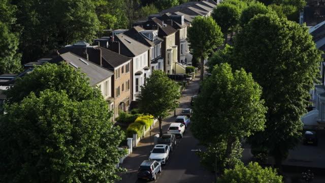 vídeos y material grabado en eventos de stock de filas de casas con coches estacionados en frente en casas residenciales adosadas en el centro de londres, reino unido - tiro de drone de alto ángulo - norte