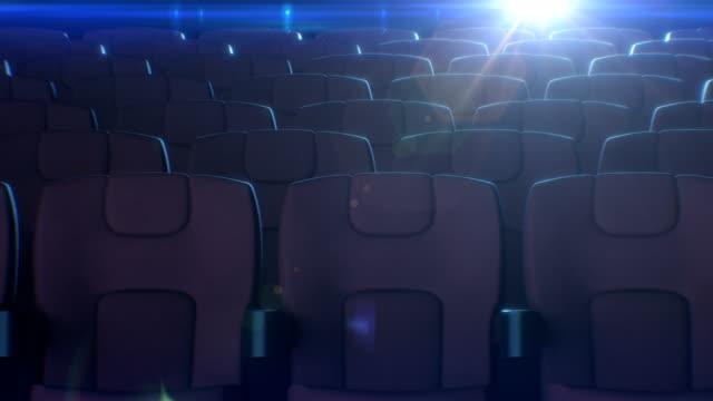 ряды красных стульев в кинозале с мигающим кинопроектором на заднем плане. 3d анимация красных сидений в кино. концепция искусства и медиа. - space background стоковые видео и кадры b-roll