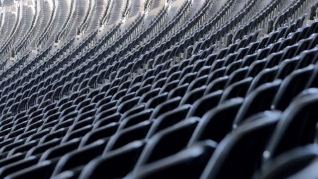rows of seats in football stadium in 4k - rack focus of many seats - mebel do siedzenia filmów i materiałów b-roll