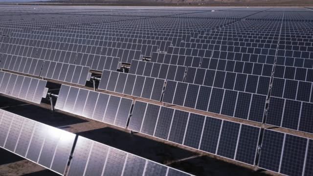 vídeos de stock e filmes b-roll de rows of solar panels in vast power station - drone shot - energia solar