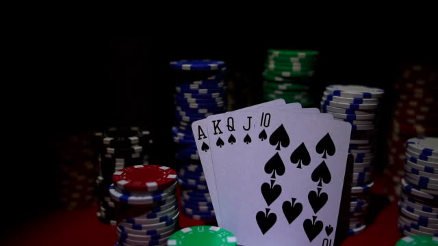 Royal flush on cards and poker chips on red casino table. video