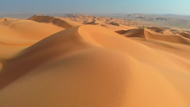 Rub' al Khali, aka Empty Quarter desert, Arabian Peninsula. Flying over curve shaped sand dunes during hot summer weather. Aerial shot, 4K