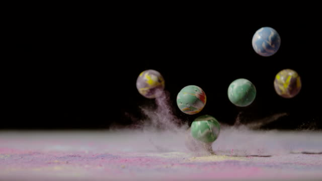 Rubber balls falling in colored powder, Ultra Slow Motion