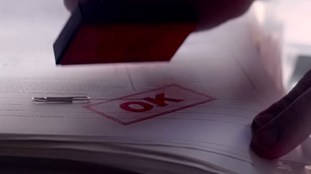 "Rubber stamping a paper document with OK    OK Close up, slow motion dolly video clip of a man's hand rubber stamping a paper document with a red inked ""OK"" stamp. The documents have passed the grade; maybe a successful application; efficient work practise or simply completed clerical work. stamp stock videos & royalty-free footage"