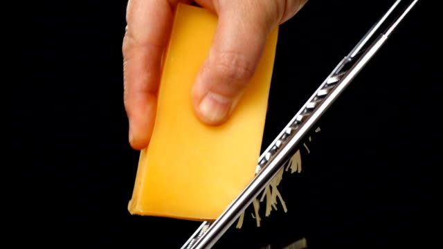 rubbing the cheese on metal grater isolated on black background - сыр стоковые видео и кадры b-roll