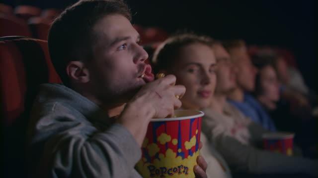 stockvideo's en b-roll-footage met onbeleefd man eten popcorn in bioscoop. ruwe omgangsvormen op filmzaal - popcorn