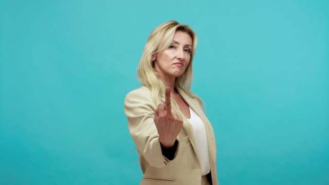 Rude unkind adult woman in business suit showing middle finger looking at camera, disrespectful offended lady saying fuck off Rude unkind adult woman in business suit showing middle finger looking at camera, disrespectful offended lady saying fuck off. Indoor studio shot isolated on blue background middle finger stock videos & royalty-free footage