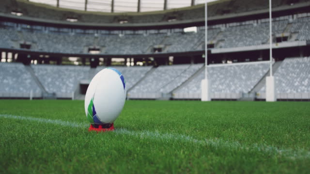 Rugby ball on a grass in the stadium 4k Close-up of rugby ball on a grass in the stadium. Empty stadium in background 4k rugby stock videos & royalty-free footage