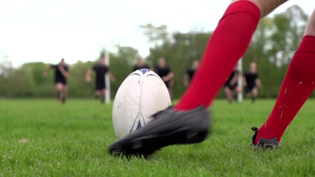 Rugby Kick Conversion through the posts (Close) - Super Slow motion Stock HD video clip footage of a Rugby match on a grass pitch. The rugby player is kicking the ball through the posts as his opponents run towards him to charge the ball down. The bright orange tee flies up in the air as he kicks the ball straight through the middle of the posts to score. Filmed at 400fps Super slow motion. Close up. rugby stock videos & royalty-free footage