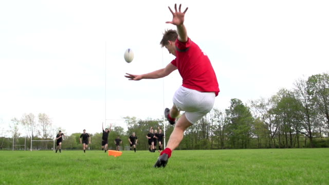 Rugby Kick Conversion through the posts - Super Slow motion Stock HD video clip footage of a Rugby match on a grass pitch. The rugby player is kicking the ball through the posts as his opponents run towards him to charge the ball down. The bright orange tee flies up in the air as he kicks the ball straight through the middle of the posts to score. Filmed at 400fps Super slow motion rugby stock videos & royalty-free footage