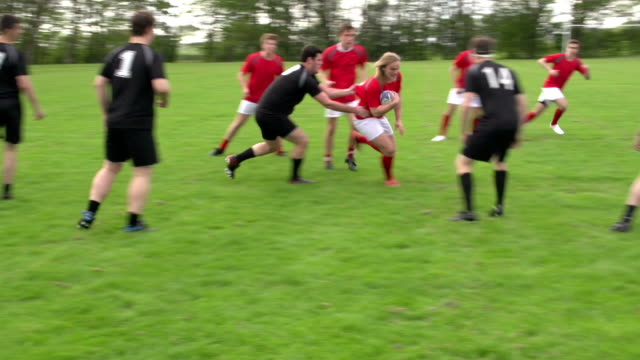 Rugby match action open play with Rucks (Sport) Stock HD video clip footage of an outdoor Rugby match on a grass pitch. There is a red team and a black team, all in full uniforms. The red team are attacking, the black team are defending. There are lots of rucks and tackles, as the red team passes the rugby ball and drive for the try line. Great sports action clip. rugby stock videos & royalty-free footage