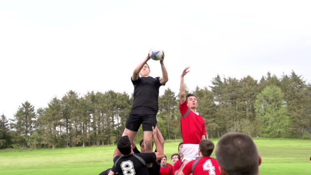 Rugby Match Lineout with ball thrown in - Super Slow motion Stock HD video clip footage of a Lineout in a rugby match. The hooker throws the rugby ball in and one of the forwards leaps the highest to retain possession of the ball. Filmed outdoors at 200 fps super slow motion. Great sports action clip, perfect for the Rugby world cup. rugby stock videos & royalty-free footage