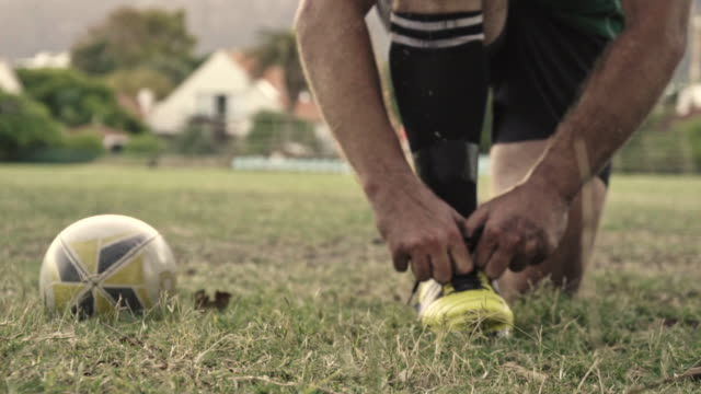 Rugby player adjusting shoelaces Closeup of a rugby player tying shoes on field with a rugby ball on the side. Rugby player adjusting his shoe laces on ground. rugby stock videos & royalty-free footage